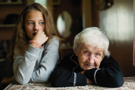 Portrait of an elderly gray-haired woman with her granddaughter.