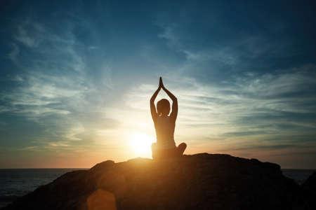 Silhouette yoga woman on the sea coast at morning beautiful sunrise. Stockfoto