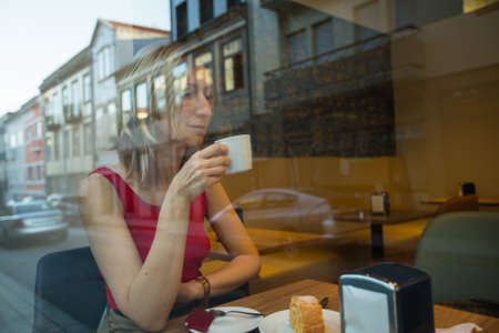 Young woman sitting in a cafe in an old city, reflection in the window.