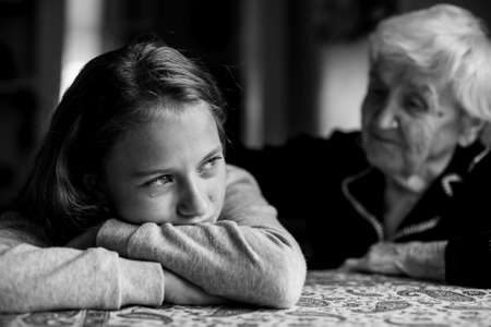 A crying little girl is comforted by her grandmother. Black and white photo. Standard-Bild