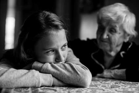 Teenage girl cries, grandmother soothes. Black and white picture.