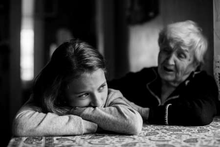 Little girl sad and grandmother soothes her. Black and white photo. Banque d'images - 131706675