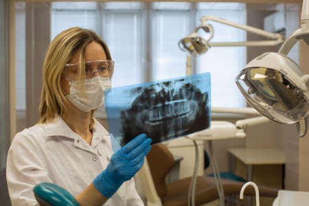 Woman dentist in dental office stares at x-ray image of tooths.