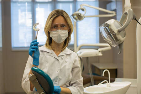Female dentist doctor shows a removable orthodontic teeth alignment and correction trainer appliance in dental office.