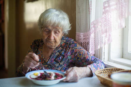 Elderly woman eating soup sitting at a table in the house.