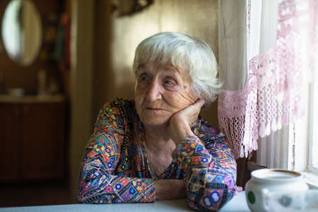 Elderly woman sitting at a table in the house. Stockfoto