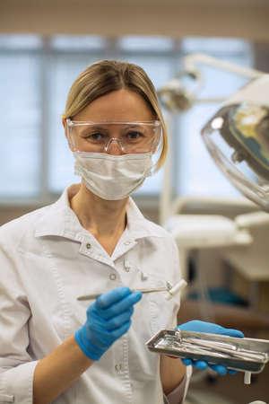 Mujer dentista con herramientas sobre antecedentes de consultorio médico. Foto de archivo