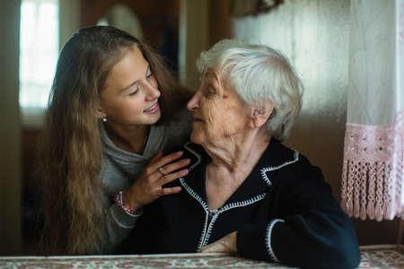 Portret van schattig klein meisje met oude dame grootmoeder.