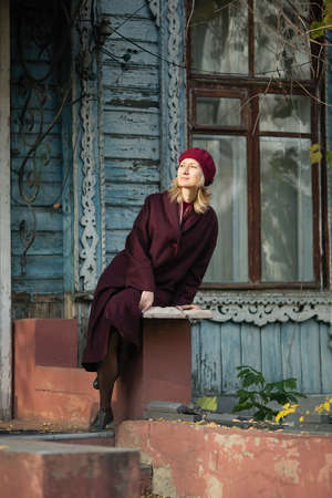Woman in a burgundy coat and beret sitting on porch of old wooden house.