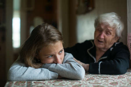 A sad little girl is comforted by her grandmother. Standard-Bild