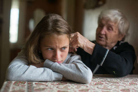 Elderly woman is spending time with her disgruntled granddaughter.