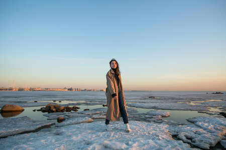 Photo shoot young woman on the shore of the Gulf of Finland in St. Petersburg in winter.
