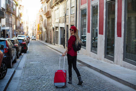 Traveler woman walking in old european town with red suitcase.