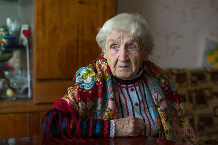 An old elderly woman in Cossack clothes in his house.