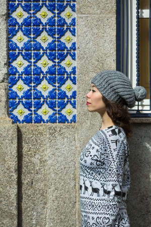 Beautiful mixed-race woman posing at profile of the house in Porto, Portugal.