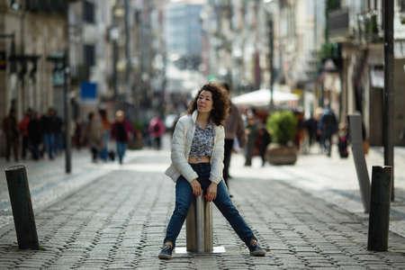 若いアジアの混血の女性は、ポルトガルのポルトの聖カタリナ通りでポーズをとっています。