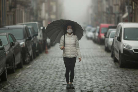 COVID-19, Coronovirus. Asian woman in antivirus mask stands in the middle of a deserted street in cloudy weather. Pandemic. Reklamní fotografie