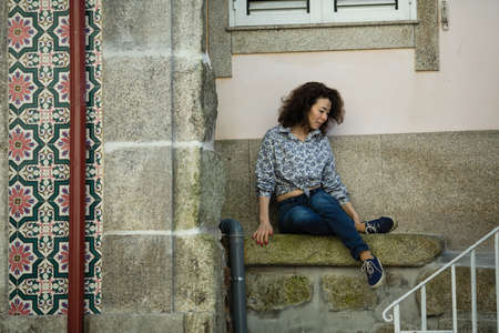 Multicultural woman sitting near the wall of the house in Porto, Portugal.