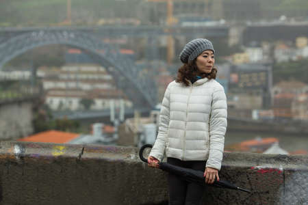 Asian woman with an umbrella on background of Dom Luis I Bridge - Porto, Portugal.