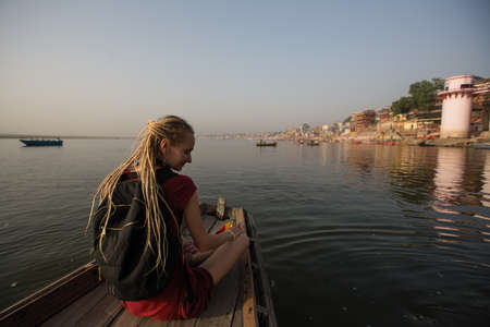 Woman traveler on a boat glides on Ganges river along the shore of Varanasi, India. Stock Photo
