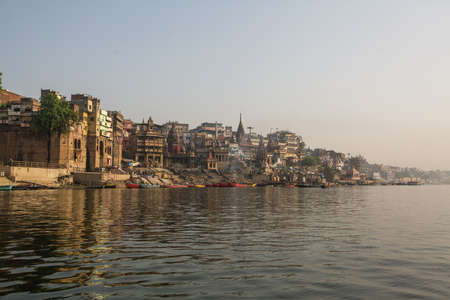 View from a boat glides through water on Ganges river along shore of Varanasi, India.