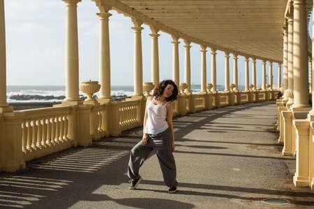 Beautiful woman dancing of sea promenade in Porto, Portugal.