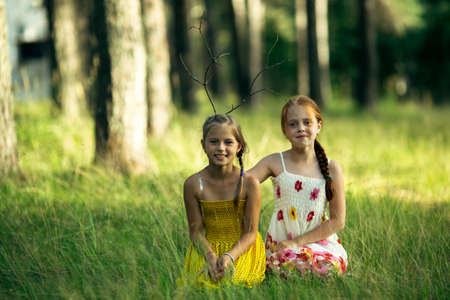 Two little girl friends posing for portrait in a pine Park.
