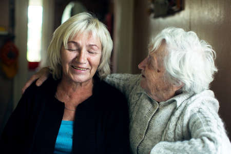 Portrait of a mature woman fooling with her old mother. Archivio Fotografico