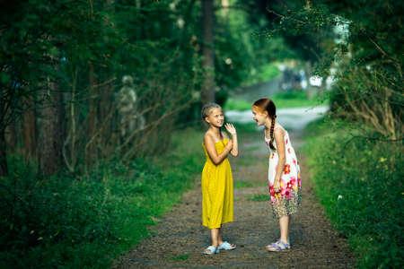 Two little girl friends gossip in a pine Park.