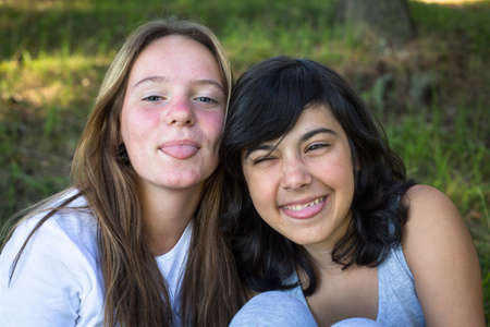 Two teenage girls fool around in front of the camera. Фото со стока