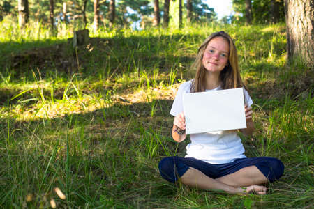 Teen girl holding clean white sheet paper, sit in the park (banner for message)