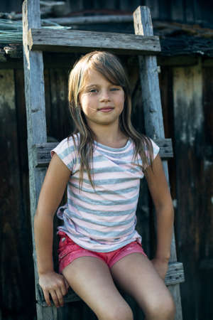 Portrait of a little girl sitting on a wooden staircase in the village. Foto de archivo