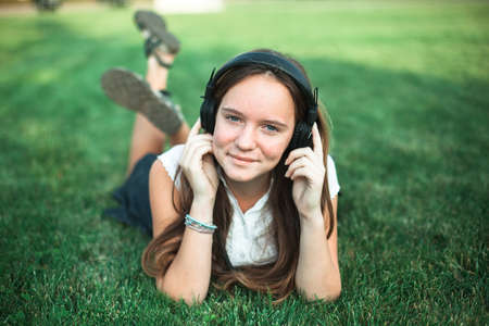 A girl lying on a green lawn enjoying music with headphones.