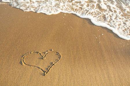 Drawn the Heart on the sand of a sea beach. Banco de Imagens