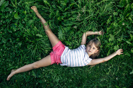 View from top. A little girl lies with her arms outstretched on the green grass.