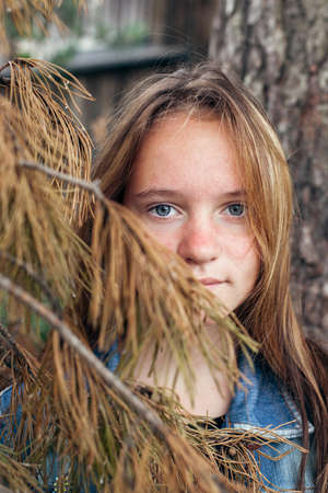 Portrait of a teenage girl near a pine tree in the Park. 免版税图像