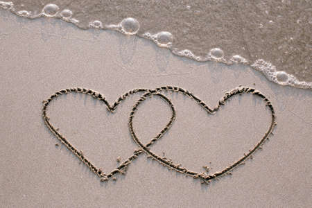 Two hearts drawn on the sand of a sea beach.
