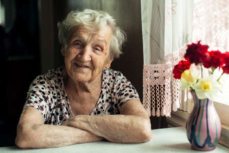 Portrait of an old woman pensioner sitting at kitchen in her home.