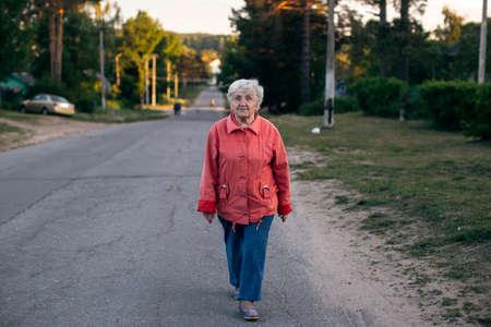 An old woman walking through the village.