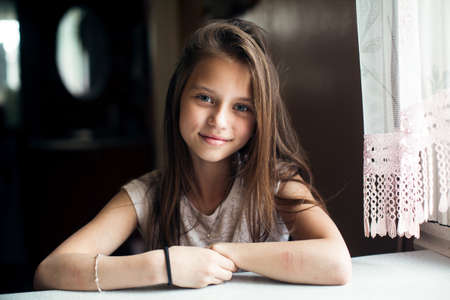 Portrait of cute little girl sitting at the table.