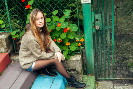 Cute teen girl poses for the camera in the park. Stock fotó
