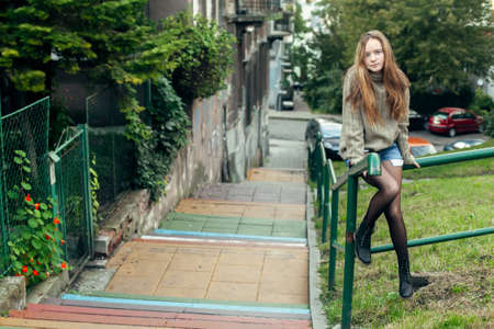 Teen girl poses for the camera in the little street. Stock fotó
