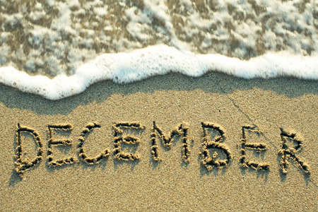 December inscription on the sand beach with the soft wave. Foto de archivo