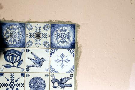 Traditional old tiles wall on the street Portuguese painted tin-glazed, azulejos ceramic tilework. Porto, Portugal. Stock Photo