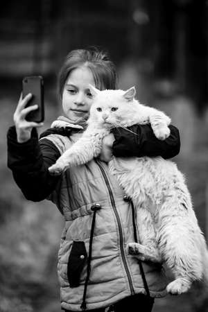 Little girl photographs herself with a stray cat on the phone. Black and white photography.