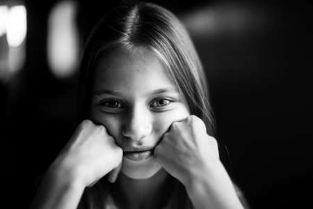 Close-up portrait of cute ten-year-old girl. Black and white photography.