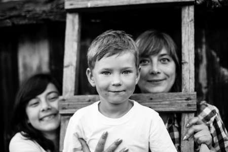 Child with his mother and older sister. Black and white photo.