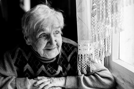 Portrait of happy old woman sitting at the table. Black and white photography. Stockfoto