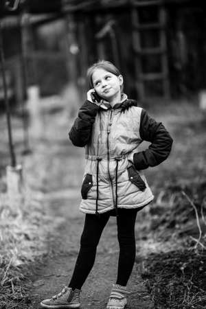 Little cute girl talking on mobile, outdoor in the village. Black and white photography.