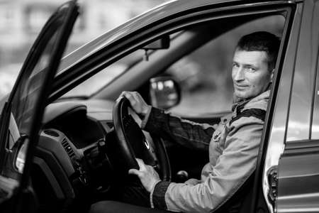 Happy man sits behind the wheel of a car. Black and white photography. Stockfoto
